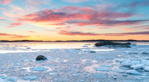 Sunset at the sea with ice and snow. Archipelago of Gothenburg, Sweden.